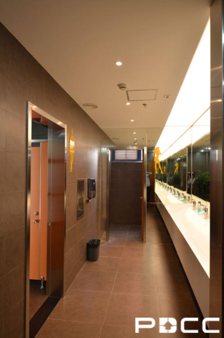 利用室外余剩面积设计一个庭院式的小憩空间,并100%采用天光照明,堪称绿色、低碳的办公室设计。  在中厅的中央位置设置为前台接待区域,圆形的前台对应圆形的吸顶灯形状,摆脱大多数公司长方形前台的俗套,而会议室全明的玻璃隔断,使空间更有了通透感。  大门入口处以黑色大理石铺地,光亮洁净,非常大气。一旁靠落地窗部位摆放奶白色沙发供顾客就坐,现代简约风格的空间设计也极其适合商务中心的特质。  办公区域的划分以玻璃隔断为主,以铁灰色为基调色,地面铺设棕色地毯,彰显商务中心沉稳、信誉的特质。  在走廊空间内利用壁饰